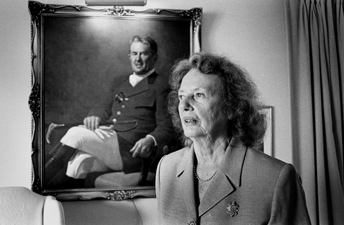 Photo Portrait of Gloria Sellar with oil painting of her husband in the background.JPG